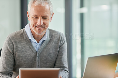 Buy stock photo Shot of a mature businessman using his digital tablet in the office