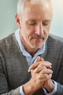 Buy stock photo Shot of a mature businessman praying while sitting in his office