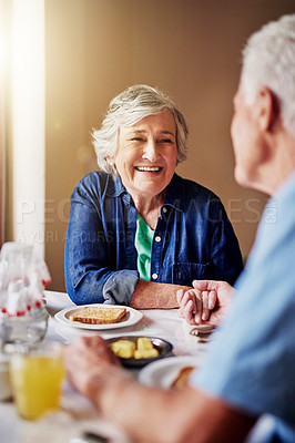 Buy stock photo Cropped shot of an affectionate senior couple eating breakfast