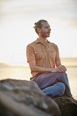 Buy stock photo Shot of a peaceful man sitting on a rock at the beach