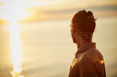 Buy stock photo Shot of a man watching the sun go down at the beach