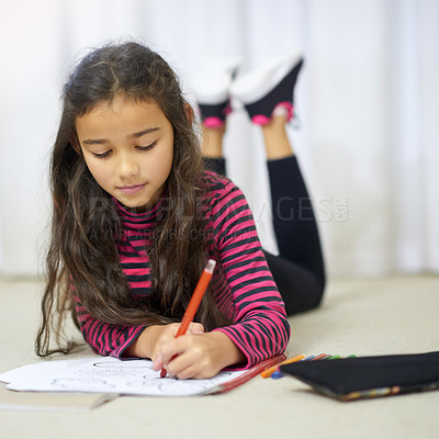 Buy stock photo Shot of a cute little girl colouring in on her own at home