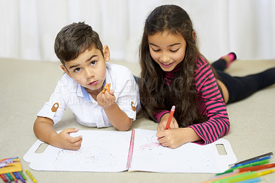 Buy stock photo Shot of a cute little boy and his sister colouring in together at home