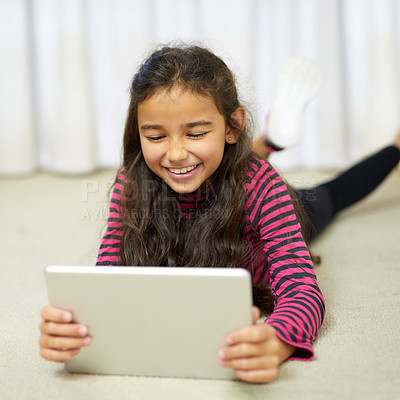 Buy stock photo Shot of a cute little girl using her tablet while lying on the floor at home