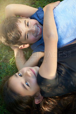 Buy stock photo Portrait of a pair of young siblings hugging each other while lying on the grass outside their home
