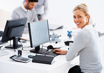 Buy stock photo Portrait of smiling business woman at desk using computer with colleagues in background