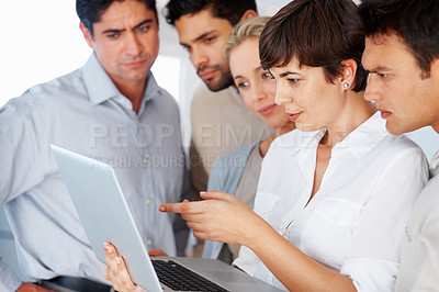 Buy stock photo Confident business woman using laptop and pointing at the screen to her colleagues