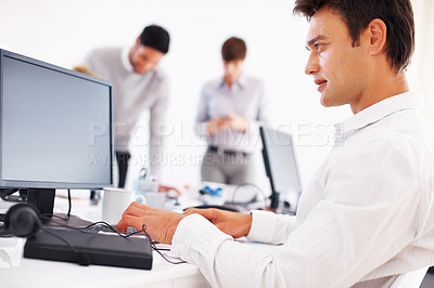 Buy stock photo Handsome business man working on computer with colleagues in background