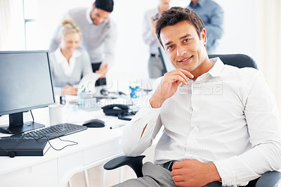 Buy stock photo Relaxed business man sitting on chair with colleagues discussing in background