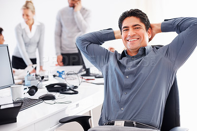 Buy stock photo Relaxed business man reclining in his chair with colleagues in background