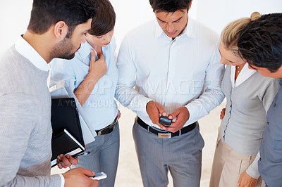 Buy stock photo Male leader with his colleagues reading text message on cell phone