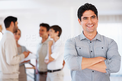 Buy stock photo Smiling business man with hands folded and colleagues discussing in background