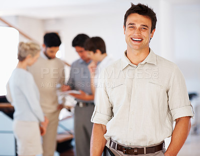 Buy stock photo Portrait of attractive business man smiling with colleagues discussing in background