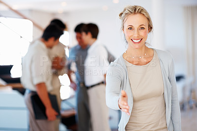 Buy stock photo Business woman offering you handshake with colleagues discussing in background