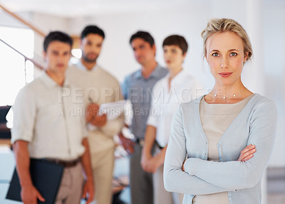 Buy stock photo Serious business woman with hands folded and colleagues discussing in background