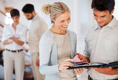 Buy stock photo Business man and woman going through project with colleagues discussing in background