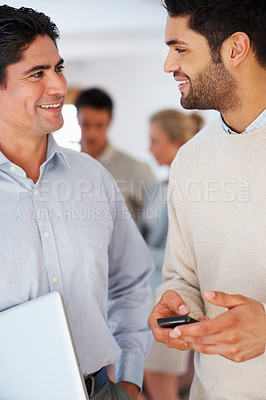 Buy stock photo Happy business men looking at each other with colleagues in background