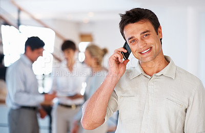 Buy stock photo Portrait of handsome business man on phone smiling and looking at you with colleagues in background