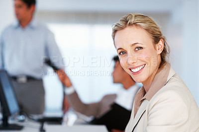 Buy stock photo Portrait of beautiful business woman smiling and looking at you with colleagues working in background