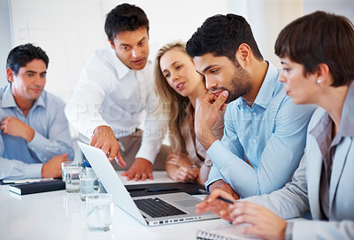 Buy stock photo Business man sitting on table and pointing at laptop during meeting