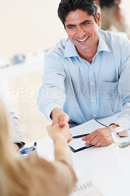 Buy stock photo Handsome business man shaking hands with female colleague and smiling