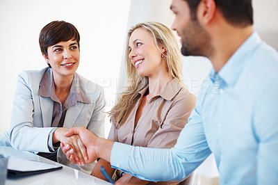 Buy stock photo Pretty female executive shaking hands with male colleague during business meeting