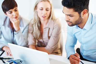 Buy stock photo Smart business man sitting at table with colleagues and using laptop