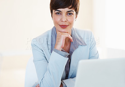 Buy stock photo Portrait of confident business woman sitting at her desk with laptop