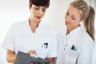 Buy stock photo Two female healthcare professionals discussing medical report of patient