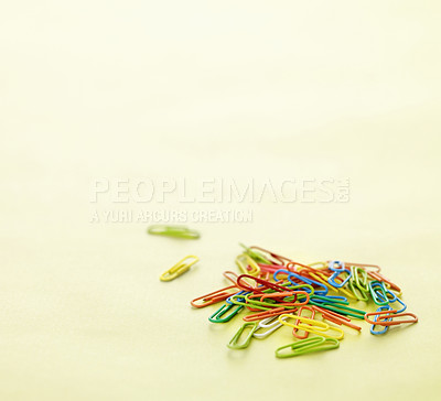 Buy stock photo Many colourful paper clips on yellow background with copyspace