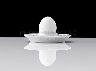 Buy stock photo One egg in a porcelain dish isolated on white table against black background