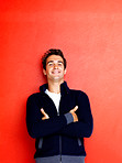 Happy young man standing with hands folded against red backgroun