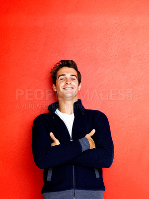 Buy stock photo Portrait of happy young man standing with hands folded against red background
