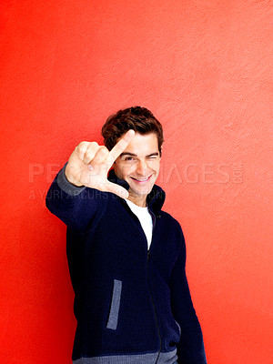 Buy stock photo Portrait of trendy young man making a loser gesture with his hand against red background