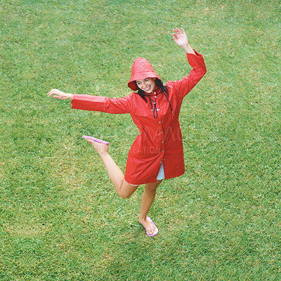 Buy stock photo Woman in raincoat dancing on grass