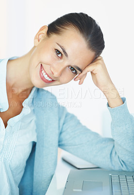 Buy stock photo Woman smiling while leaning head on hand in front of laptop