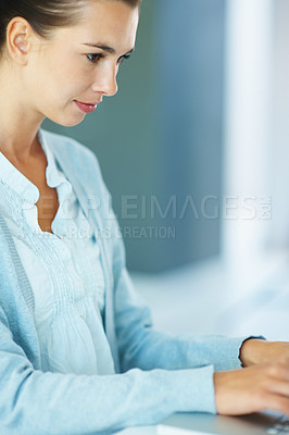 Buy stock photo Serious woman sitting and working on laptop