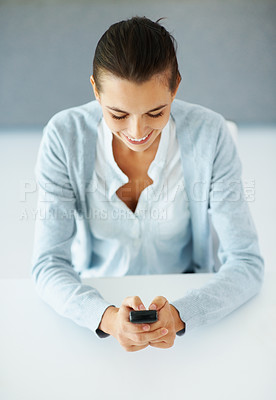 Buy stock photo Top view of smiling woman texting on mobile