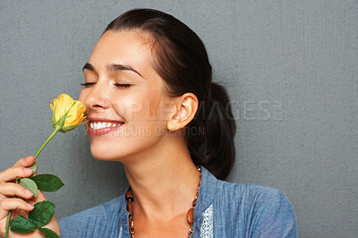 Buy stock photo Pretty woman smelling yellow rose with eyes closed