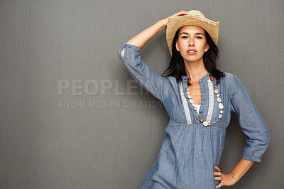 Buy stock photo Pretty woman standing and holding cowboy hat while leaning against wall