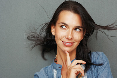 Buy stock photo Pretty woman holding finger up to chin and looking mischievous