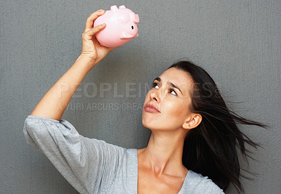 Buy stock photo Pretty woman holding piggy bank upside down
