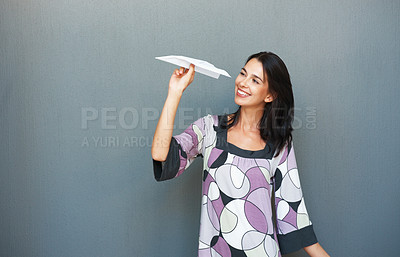Buy stock photo Pretty woman holding paper airplane and smiling