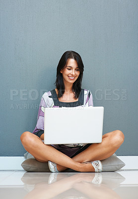 Buy stock photo Happy woman sitting on cushion with laptop in lap