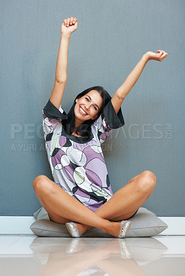 Buy stock photo Happy woman extending her arms while sitting on a cushion
