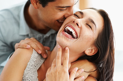 Buy stock photo Closeup of a young couple embracing and laughing