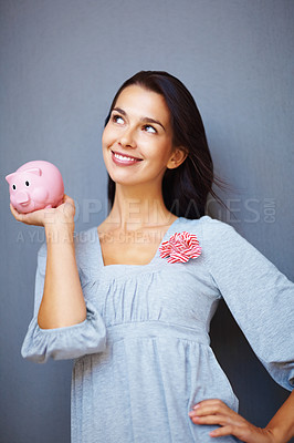 Buy stock photo Happy young woman holding piggy bank in hand