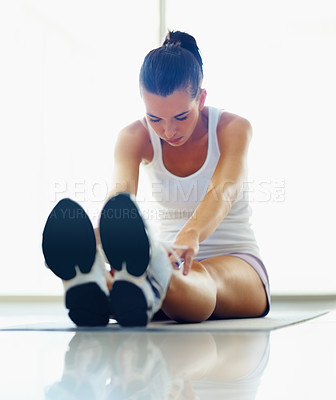 Buy stock photo Pretty woman at the gym doing stretching exercise