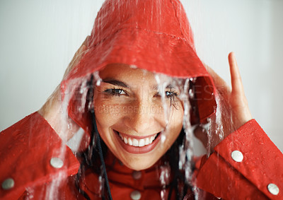 Buy stock photo Closeup of happy young girl holding hat in rain