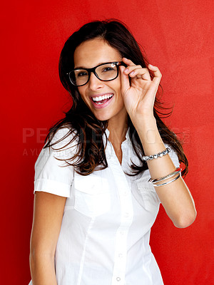 Buy stock photo Portrait of a happy young woman wearing black-framed glasses against a red background